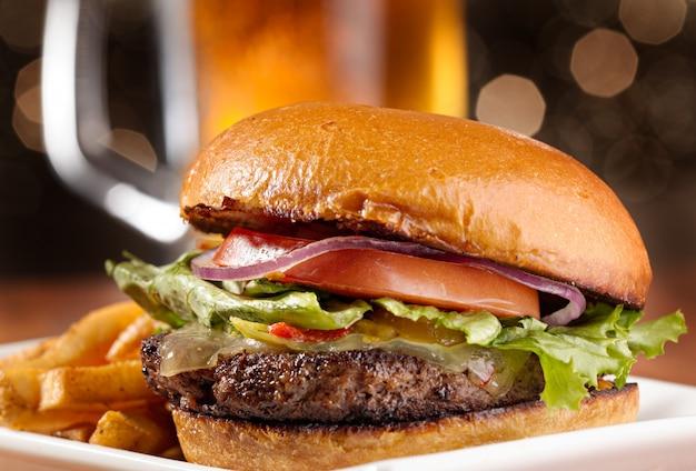 Gourmet-cheeseburger mit bierkrug im hintergrund