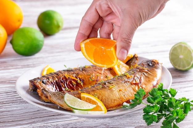 Gourmet-essen: gebackener fisch mit limetten- und orangenscheiben mit orangensauce auf einer teller-nahaufnahme. horizontal