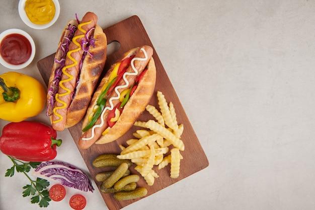 Gourmet gegrillt alle rindfleisch hot dog mit beilagen und pommes. leckere und einfache hot dogs mit senf, pfeffer, zwiebeln und nachos. hot dogs voll beladen mit verschiedenen belägen auf einem paddle board.