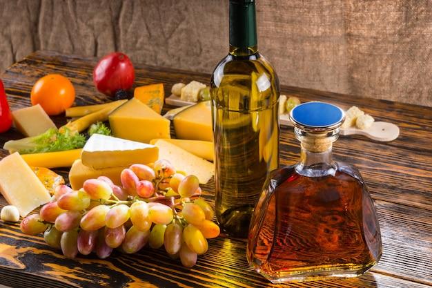 Gourmet-käseplatte mit einer großen auswahl an verschiedenen käsesorten und alkoholischen getränken auf einem buffet bei einer party
