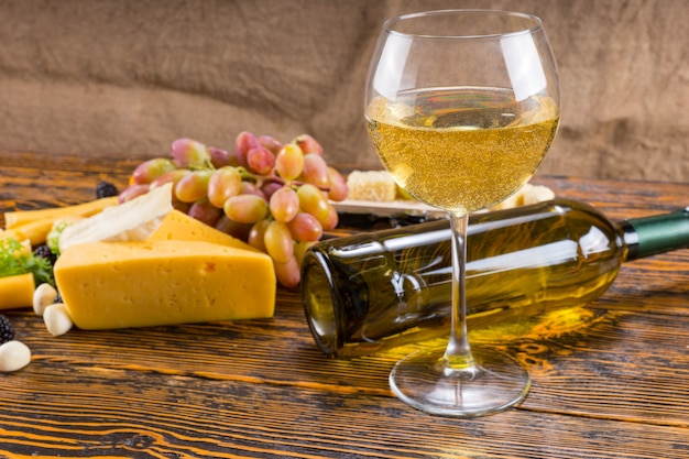 Gourmet-lebensmittel-stillleben - glas weißwein auf rustikalem holztisch mit gefallener flasche und verschiedenen käsesorten und trauben