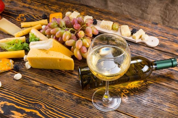 Gourmet-lebensmittel-stillleben - nahaufnahme von glas weißwein mit gefallener flasche zwischen verschiedenen käsesorten und frischem obst auf rustikalem holztisch mit textfreiraum