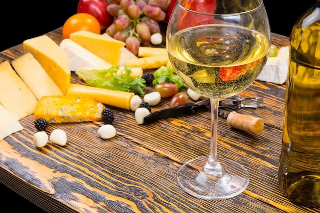 Gourmet-lebensmittel-stillleben - nahaufnahme von glas weißwein unter verschiedenen käsesorten und frischem obst auf rustikalem holztisch mit textfreiraum
