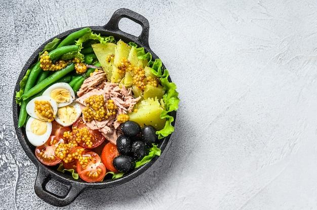 Gourmet-nicoise-salat mit gemüse, eiern, thunfisch und sardellen in einer pfanne.