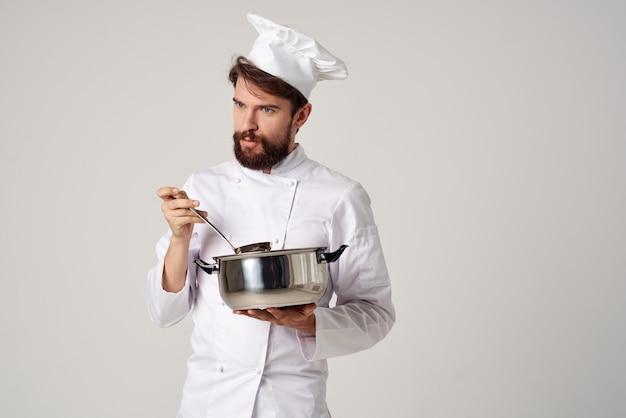 Gourmetrestaurant des männlichen chefkochs, das hellen hintergrund kocht
