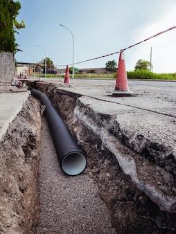 Graben mit neuen wasserleitungen im boden einer wohnstraße. öffentliches arbeitskonzept.
