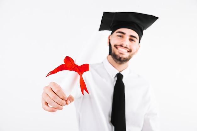 Graduierender mann, der diplom zeigt