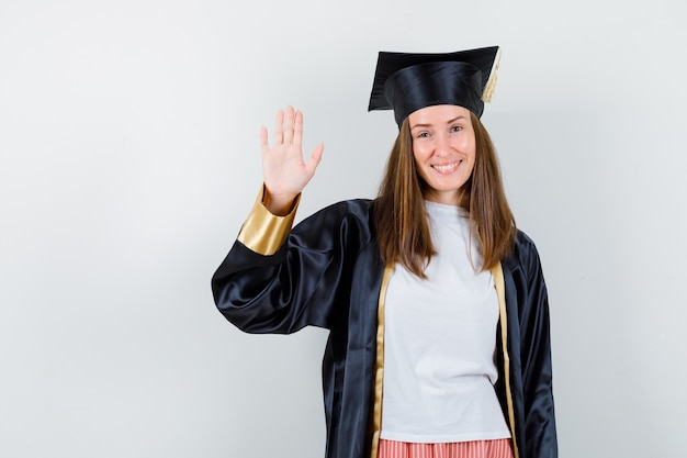 Graduierte frau, die hand für begrüßung in freizeitkleidung, uniform und freudig aussehend winkt. vorderansicht.