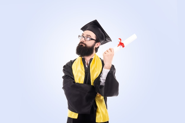 Graduierter mann, der das diplom über dem ernsten gesicht der blauen wand hält, das über frage nachdenkt, sehr verwirrte idee