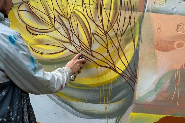Graffiti-künstler malt bunte graffiti auf eine betonwand. städtisches konzept der modernen kunst