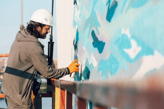 Graffiti-künstler malt eine weiße wand in großer höhe in wellen.