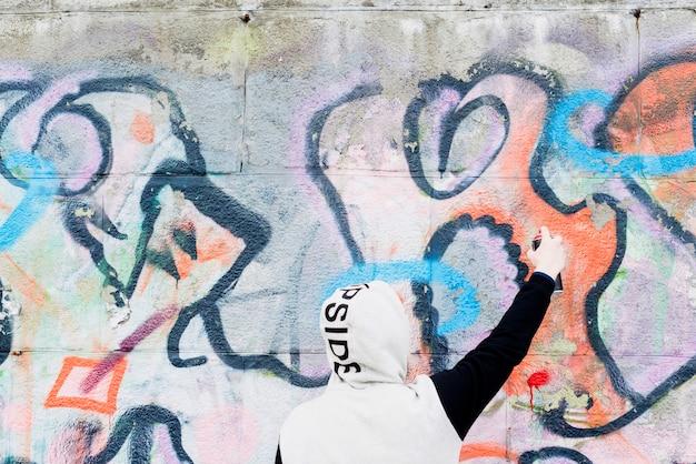 Graffitikünstler, der abstrakte malerei auf wand zeichnet