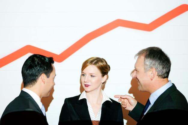 Grafik an der wand mit business-team mit grafik (beamer als lichtquelle!)