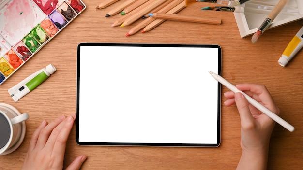 Grafik-künstler-arbeitsplatz-nahaufnahme hände skizzieren auf grafiktablett-modell auf holztisch-draufsicht