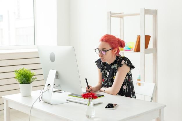 Grafikdesigner, animator und illustrator-konzept - junge frau mit roten haaren, die am laptop arbeiten.