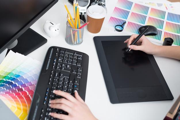 Grafikdesigner-arbeitsplatz während weibliche hände arbeiten