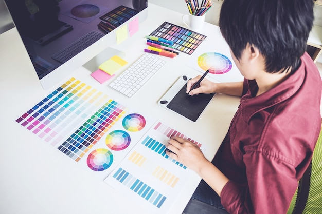 Grafikdesigner, der an farbauswahl arbeitet und auf grafiktablett am arbeitsplatz zeichnet
