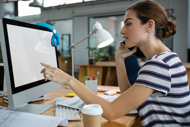 Grafikdesigner, der computer beim sprechen auf mobiltelefon verwendet