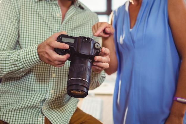 Grafikdesigner, der dem kollegen foto auf digitalkamera zeigt