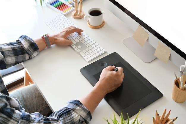 Grafikdesigner, der digitale tablette mit tischrechner im studiobüro verwendet