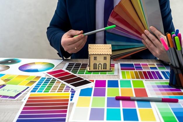 Grafikdesigner, der eine farbe aus einem sampler im büro auswählt. farbfelder. mannhände, die eine farbe von einem probenehmer wählen