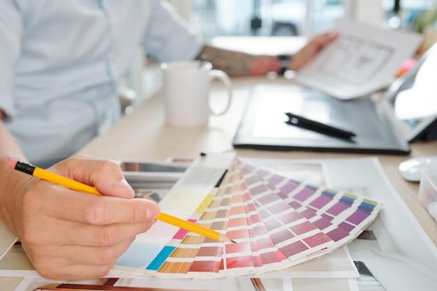 Grafikdesigner, der farbe in der palette auswählt, wenn er an einem projekt für den kunden arbeitet
