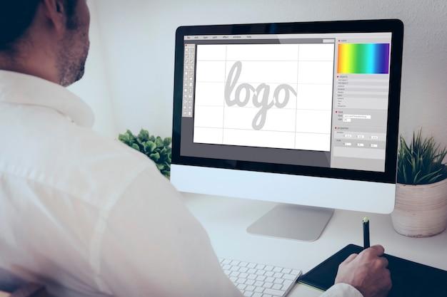 Grafikdesigner, der mit computer und grafikstift arbeitet