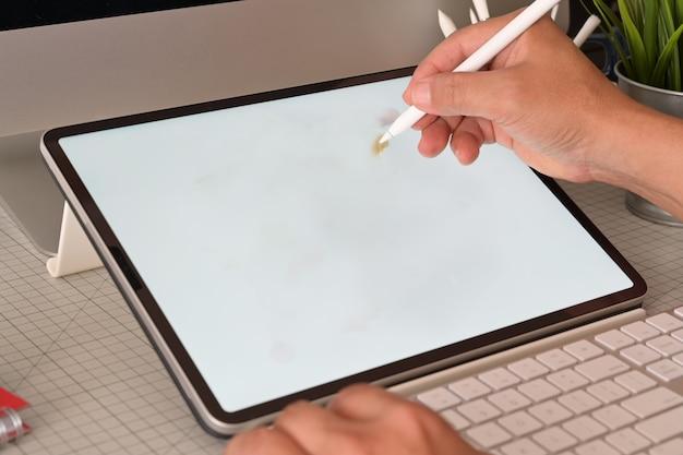 Grafikdesigner, der mit digitaler zeichnungstablette am studioarbeitsplatz arbeitet.