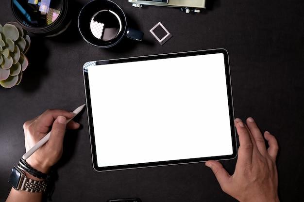 Grafikdesigner, der mit digitaler zeichnungstablette auf dunklem schreibtisch arbeitet