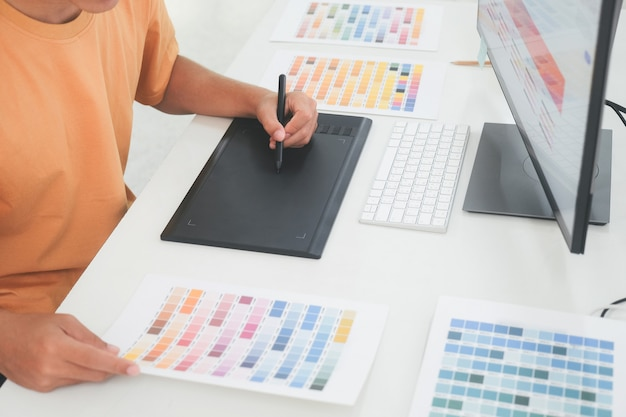 Grafikdesigner, der mit farbmustern zur auswahl arbeitet. grafikdesigner bei der arbeit. muster von farbmustern. junger fotograf und grafikdesigner bei der arbeit im büro.