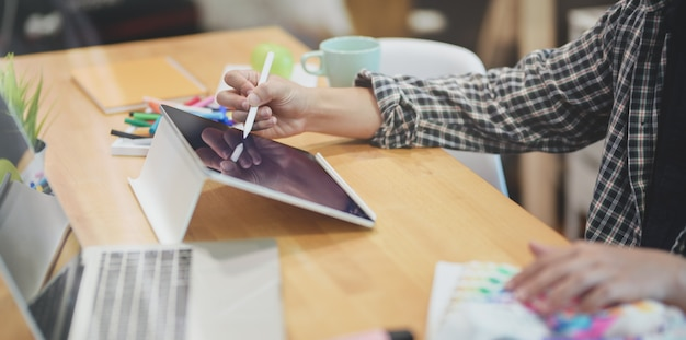 Grafikdesigner, der seine ideenkonzepte auf tablette schreibt