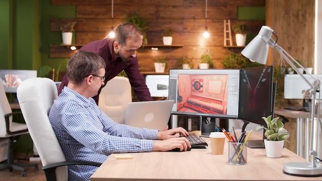 Grafikdesigner in der spieleindustrie, der in seinem büro sitzt und videospielgrafiken diskutiert