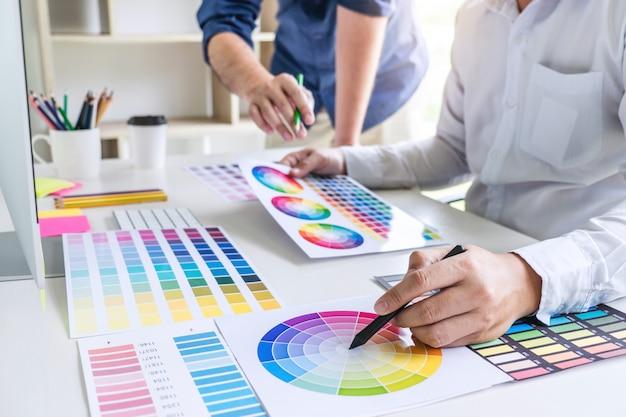 Grafikdesigner mit zwei kollegen, der an farbauswahl und farbmustern arbeitet