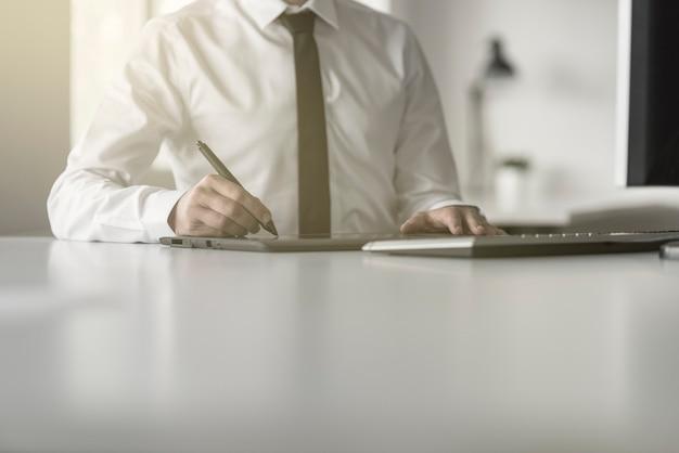 Grafikdesigner oder fotograf, der ein tablet und einen stift für die fotobearbeitung oder postproduktion verwendet.