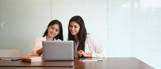 Grafikdesigner-team, das mit einem computer-laptop am schreibtisch zusammenarbeitet