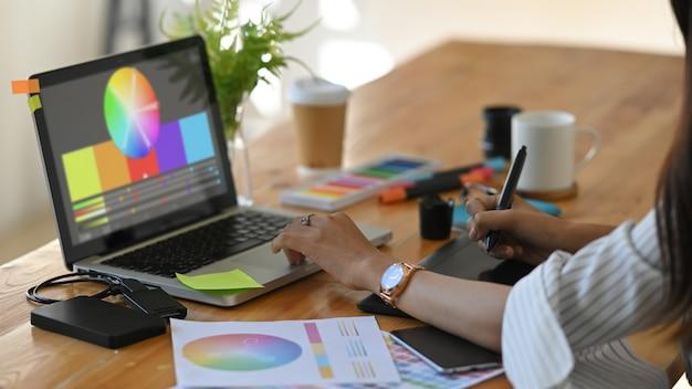 Grafikdesignerin wählt farbe mit laptop und kreativem zubehör auf dem tisch.