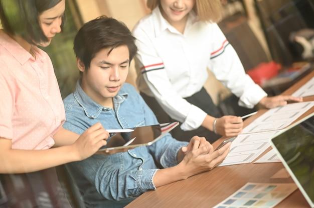Grafikdesignerteam arbeitet im büro. sie benutzen laptop und tablet.