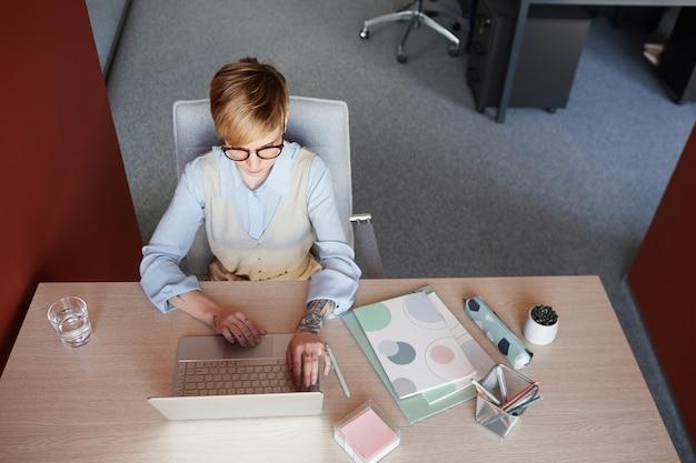 Grafische ansicht von oben nach unten an der modernen tätowierten geschäftsfrau unter verwendung des laptops am schreibtisch während der arbeit im büro, kopierraum