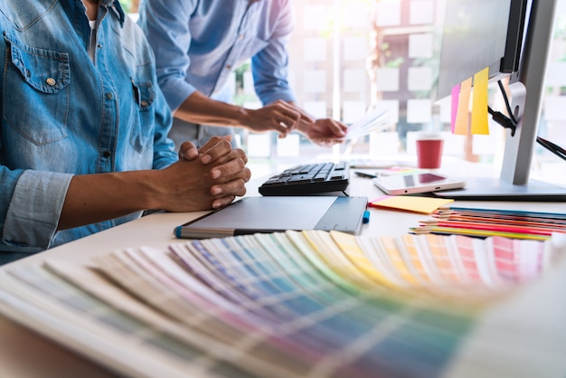Grafische kreative kreativität des designers, die zusammenarbeitet, färbend unter verwendung der grafiktablette und eines griffels am schreibtisch mit kollegen.