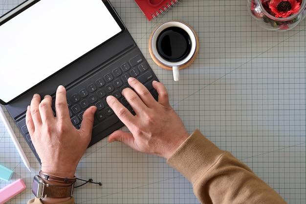 Grafischer designer, der mit tastaturtablette im studio schreibt.