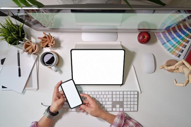 Grafischer kreativer designer, der handy verwendet und mit grafiktablett der digitalen anzeige arbeitet