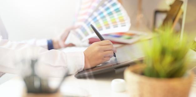 Grafischer kreativer designer, der im studiobüro arbeitet