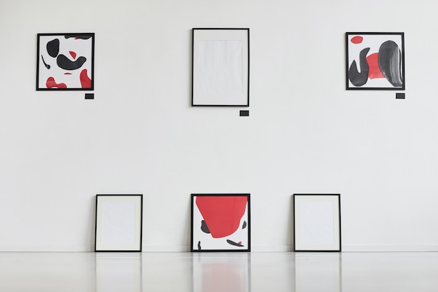 Grafisches hintergrundbild von modernen abstrakten gemälden mit schwarzweiss, die an weißer wand in der kunstgalerie-ausstellung hängen,