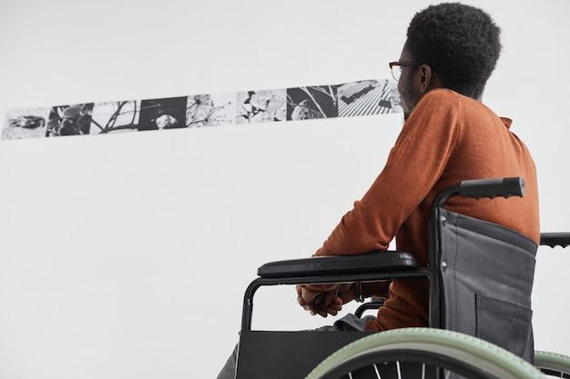 Grafisches porträt des jungen afroamerikanischen mannes, der rollstuhl benutzt und gemälde beim erkunden der galerieausstellung der modernen kunst betrachtet,