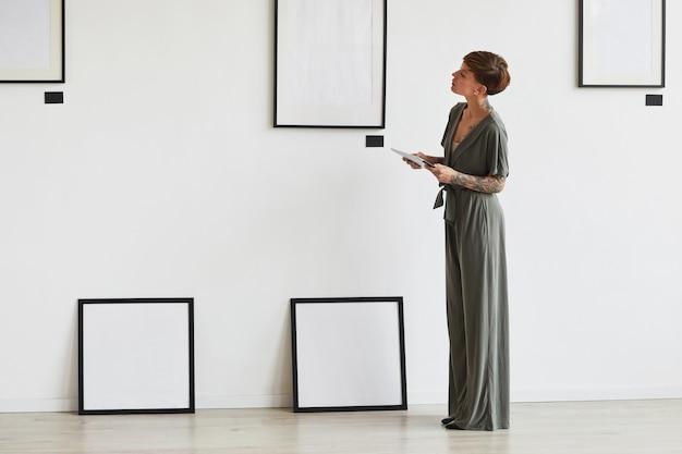 Grafisches porträt in voller länge des eleganten weiblichen kunstgaleriemanagers, der rahmeneinstellung während der planung der ausstellung oder des ereignisses betrachtet,
