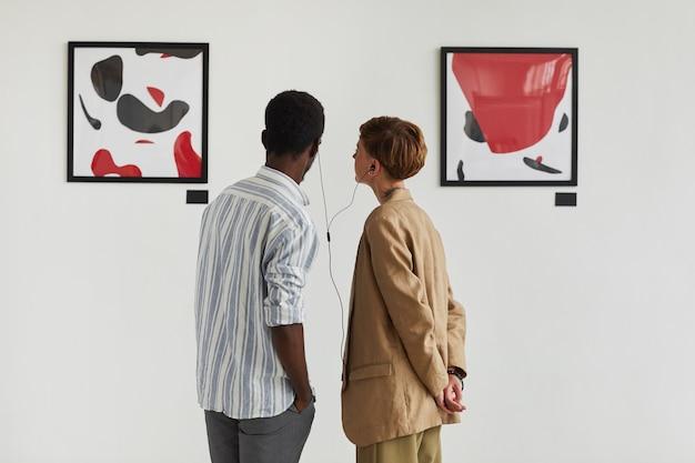 Grafisches rückansichtporträt von zwei jungen leuten, die gemälde betrachten und audioguide teilen, während sie moderne kunstgalerie-ausstellung erkunden