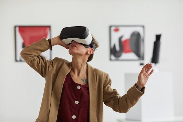 Grafisches taillen-hochporträt der modernen jungen frau, die vr-ausrüstung trägt, während immersive erfahrung an kunstausstellungsausstellung genießt