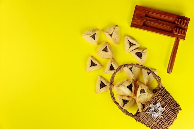 Gragger mit keksen auf gelbem hintergrund. jüdischer feiertag purim.