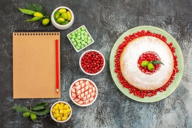 Granatäpfel ein appetitlicher kuchen notizbuch bleistift schalen mit limetten verschiedene süßigkeiten