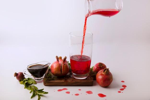 Granatäpfel mit roter sauce und saft auf einem holzbrett